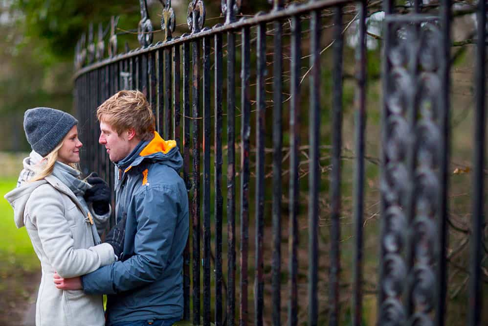 Dunfermline engagement photography couple standing next to fence