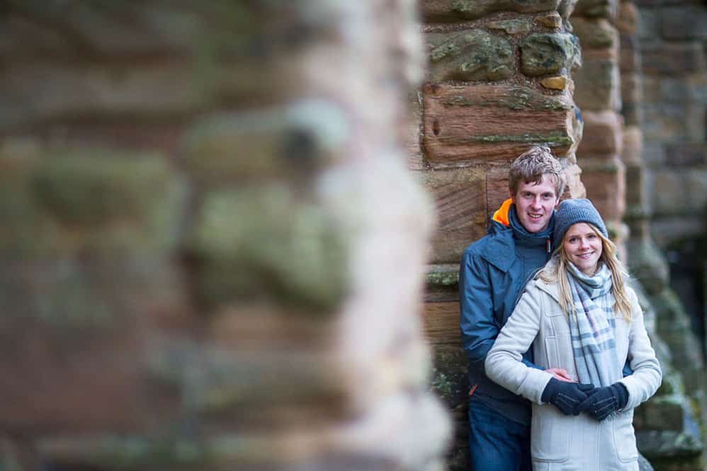 Dunfermline engagement photography hugging couple next to wall