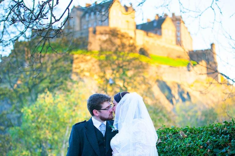 groom and bride kissing under edinburgh castle