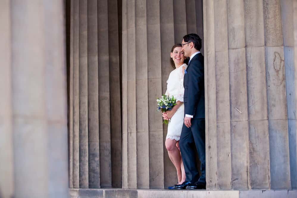 relaxed bride and groom with national gallery pilars in edinburgh