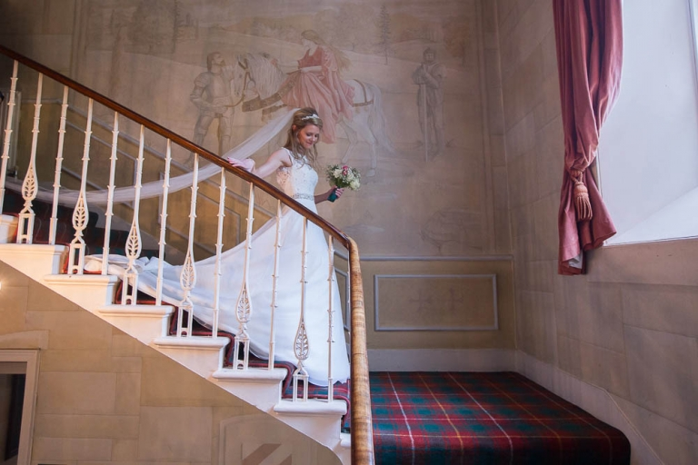 Fernie Castle bride walking downstairs with very long veil