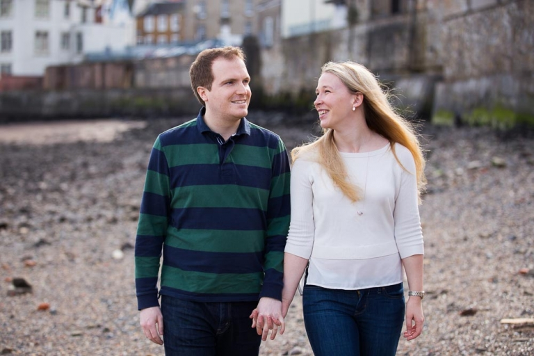 engagement photographer Edinburgh, happy couple walking on beach in South Queensferry