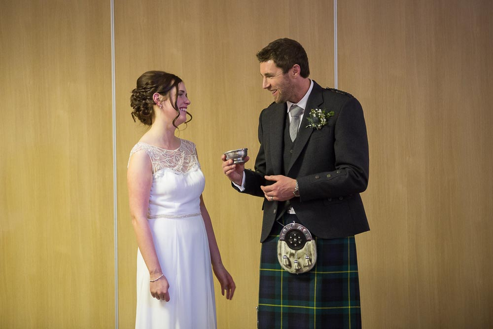 highland wedding photographer, groom sharing with bride cup of whisky