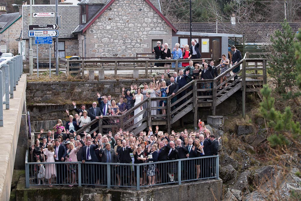 highland wedding photographer, wedding party next to carrbridge village bridge