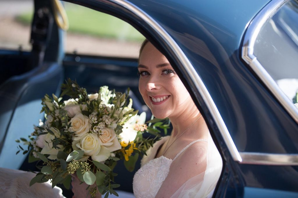 bride looking out from the vintage car